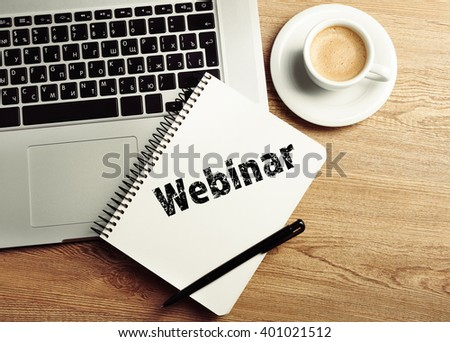 Webinar written in notebook, laptop and cup of coffee on table, top view - stock photo