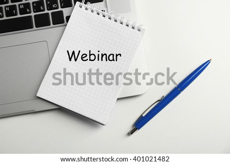 Webinar written in notebook, laptop and pen on table, top view - stock photo