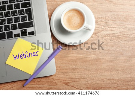 Webinar written on sticky note, laptop and cup of coffee on table, top view - stock photo