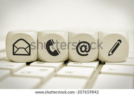 Website and Internet contact us page concept with black icons on keyboard - stock photo