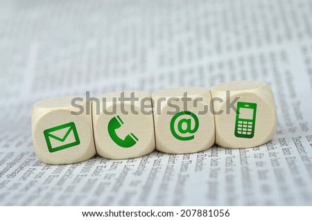 Website and Internet contact us page concept with green icons on a newspaper  - stock photo