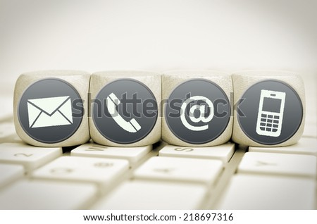Website and Internet contact us page concept with white icons on cubes on a keyboard - stock photo