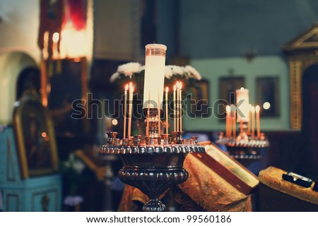Wedding accessories and interior in Saint Trinity Orthodox Convent including two candlesticks with many candles, flowers, icons and Holy Bible. Wonderful church in Riga, Latvia - stock photo