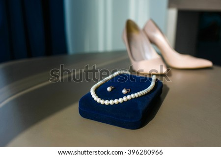 Wedding accessories of the bride. Necklaces and earrings of pearls on blue velvet box. Wedding beige shoes - stock photo