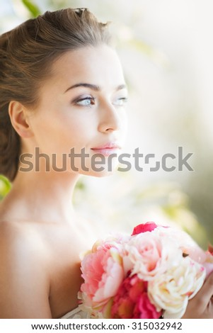 wedding and beauty concept - young woman with bouquet of flowers - stock photo