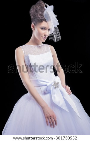 Wedding and Fashion Concept. Portrait of Young Caucasian Female Lady in Tailored Wedding Dress Made to Order Against Black. Vertical Image Composition