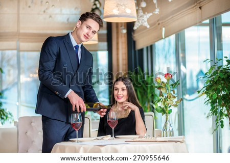 Wedding Anniversary Celebration at the restaurant. Romantic dinner in the restaurant. Young loving couple visiting the restaurant while her husband was poured into a glass of wine - stock photo