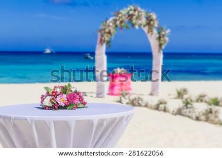 wedding arch and flower decoration, venue, setup on tropical beach, outdoor beach wedding  - stock photo