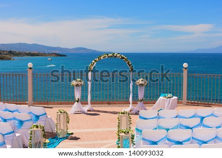 wedding arch and set up by the sea - stock photo