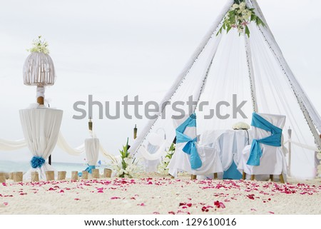 wedding arch, decorated table and set up on beach - stock photo