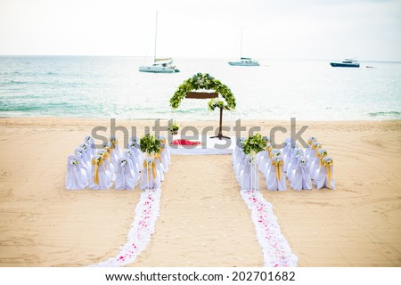 wedding arch decorated with flowers on tropical sand beach, outd - stock photo