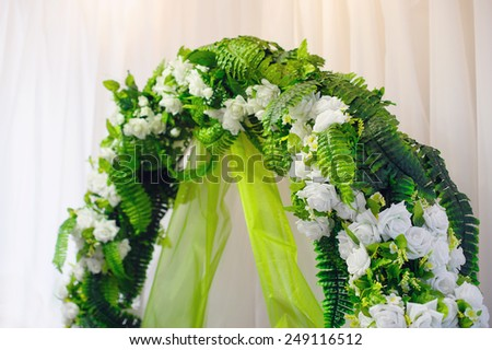 wedding arch decorated with green flowers. - stock photo