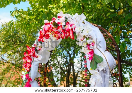 wedding arch decorated with pink orchids. - stock photo