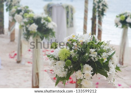 wedding arch, flower posts and decoration on beach - stock photo