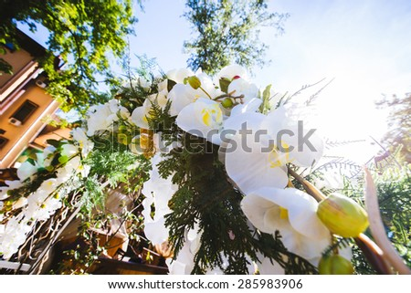 wedding arch outdoors decorated with flowers - stock photo