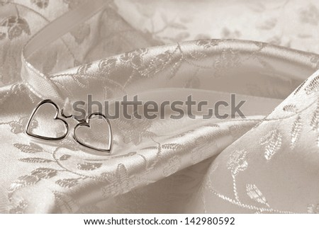 Wedding background of two silver hearts joined together with ribbon on elegant satin brocade fabric. Sepia toned macro with extremely shallow dof. - stock photo