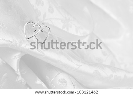 Wedding background of two silver hearts joined together with ribbon on elegant white satin brocade fabric.  Macro with extremely shallow dof. - stock photo