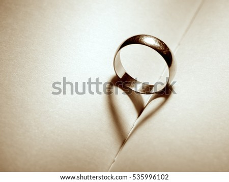 Wedding band casting shadow of a heart on to the pages