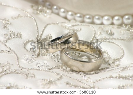 wedding bands sitting on top of richly embroidered wedding dress - stock photo