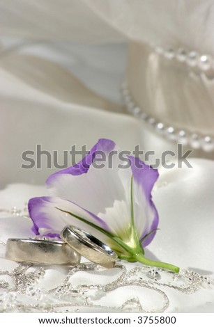 wedding bands sitting on top of richly embroidered wedding dress with white and purple flower - stock photo