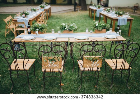 Wedding. Banquet. Chairs and honeymooners table decorated with candles, served with cutlery and crockery and covered with a tablecloth. The table stands on a green lawn in the backyard banquet area - stock photo
