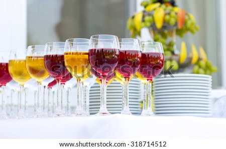 Wedding banquet outdoors. Wedding ceremony. Glasses of red and white wine. Glass of champagne - stock photo