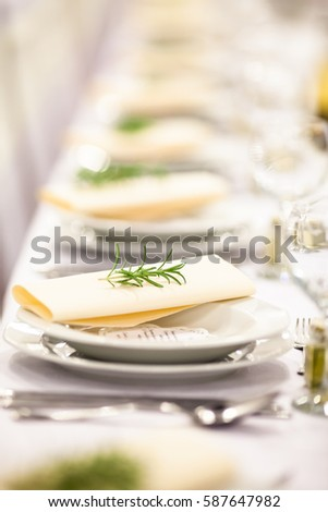 Wedding. Banquet. The chairs and table for guests, decorated with candles, served with cutlery and crockery and covered with a tablecloth.