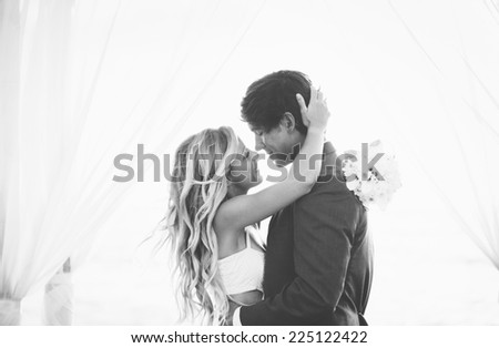 Wedding, Beautiful Romantic Bride and Groom Kissing and Embracing at Sunset. Black and White Image. - stock photo