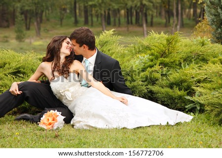 wedding, beautiful young bride lying together with groom in love on green grass kissing, park summer outdoor - stock photo
