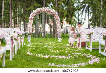 Wedding benches with guests and flower arch for ceremony outdoors - stock photo