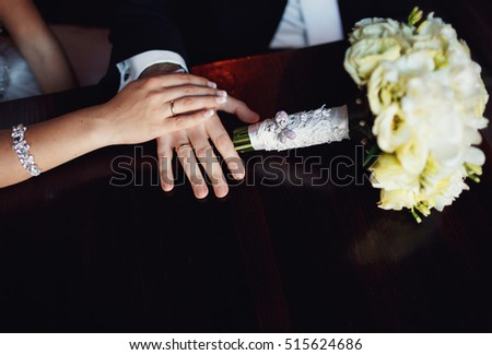 Wedding bouquet and hands of the newlyweds on the table