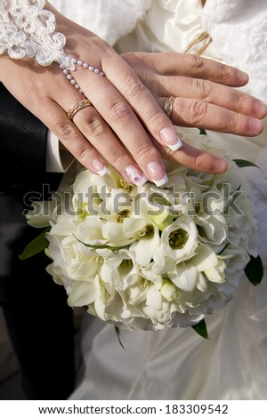 Wedding bouquet and hands with rings. White flowes.