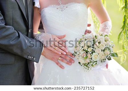 wedding bouquet and rings with bride and groom - stock photo