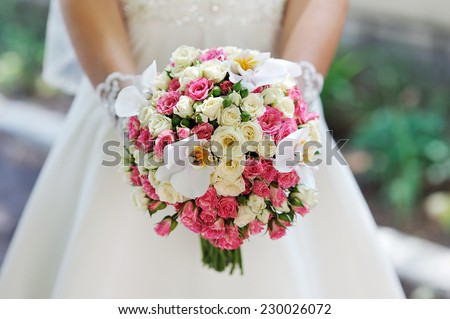 wedding bouquet at bride's hands. studio shot. - stock photo