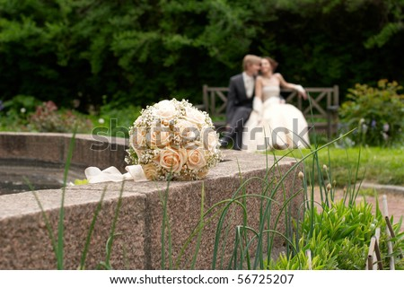 Wedding bouquet downstage with bride and groom in background - stock photo