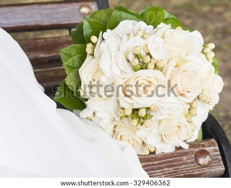 Wedding  bouquet  lying on the bench near the bride