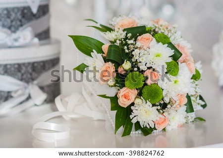Wedding bouquet made of roses, chrysanthemum and laying on the table