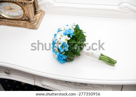 Wedding  bouquet near a vintage gold clock on a white surface - stock photo