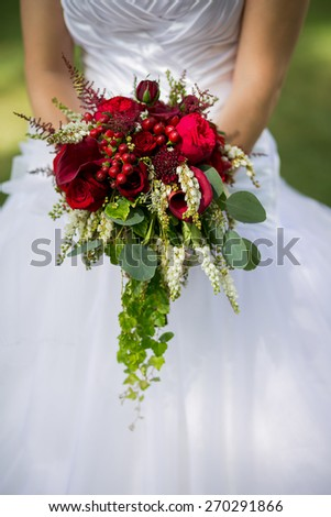 Wedding bouquet of flowers including Red hypericum, Roses, Lilies of the valley, mini Roses, Seeded Eucalyptus, Astilbe, Scabiosa, Pieris, and ivy - stock photo