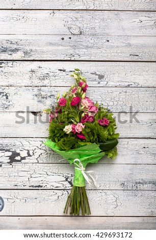 Wedding bouquet of pink and white roses and blue fresia lying on wooden floor. Nice bouquet of flowers for your friends or people in love. - stock photo