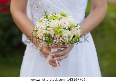 wedding bouquet of roses in the hands of the bride