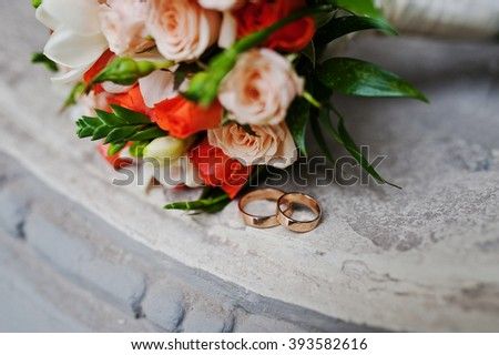 Wedding bouquet of white and orange roses and with two wedding rings on antique window