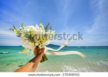 Wedding bouquet of white flowers in hand . Against the background of blue sea and tropical islands . - stock photo
