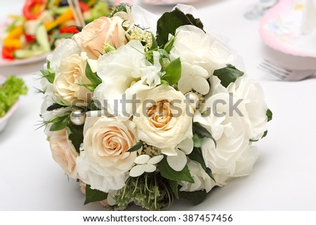 Wedding bouquet of white roses lying on the holiday table