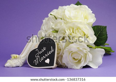 Wedding bouquet of white roses with good luck high heel shoe and heart sign with Just Married message, against purple lilac background. - stock photo