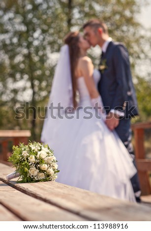 Wedding bouquet on a background of the bride and groom (bokeh) - stock photo