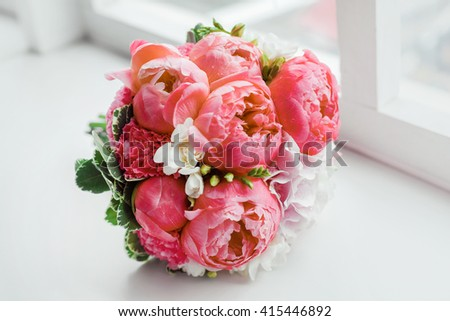 Wedding bouquet on window sill. Bride's traditional symbolic accessory. Floral composition with red celosia flowers. - stock photo