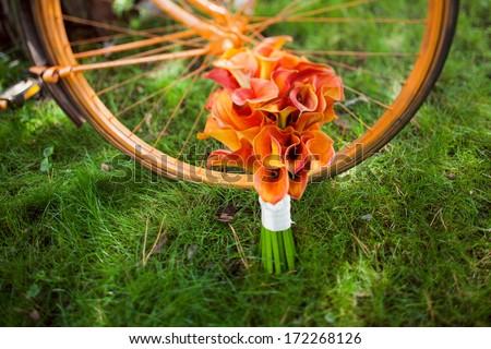 wedding bouquet orange calla and orange bike - stock photo