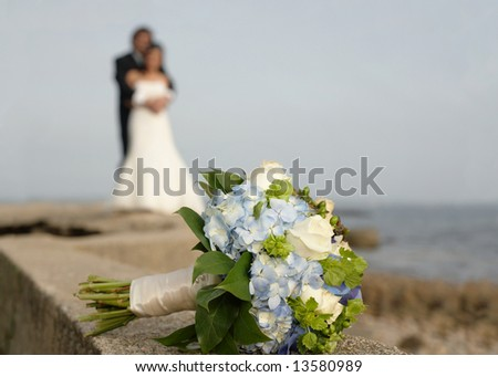 Wedding bouquet with bride and groom in background