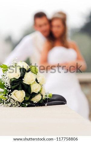 Wedding bouquet with Bride and Groom on background in portrait orientated photo, focused to the Wedding bouquet - stock photo